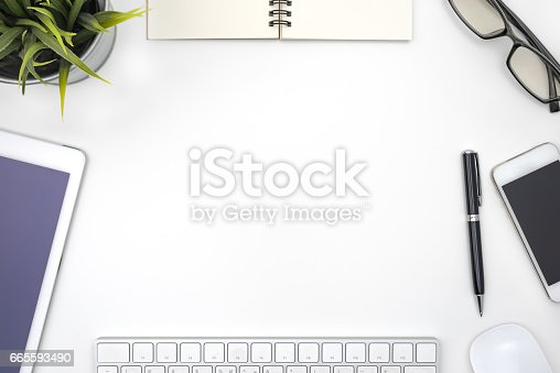 istock Frame with office equipment on white desk 665593490