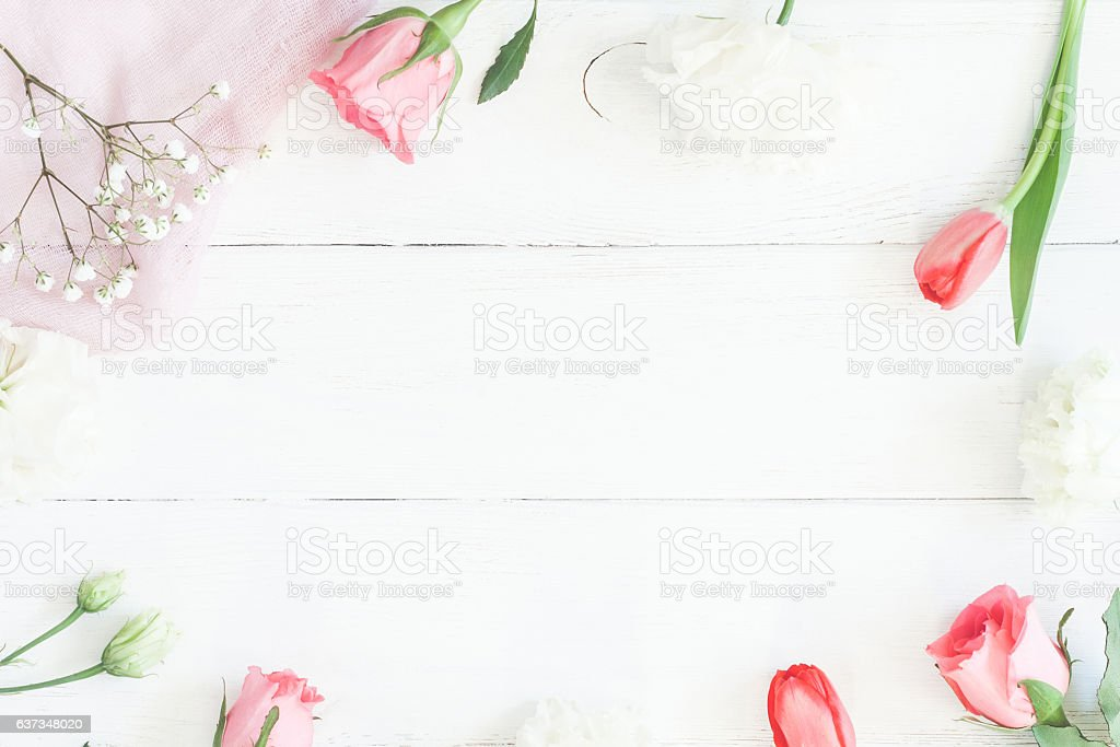 Frame with rose flowers and tulip om wooden white background