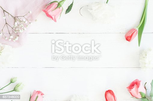 istock Frame with rose flowers and tulip om wooden white background 637348020