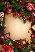 istock Frame with vintage paper, fir branches, cookies and Christmas decorations on dark wooden background. 1174658675
