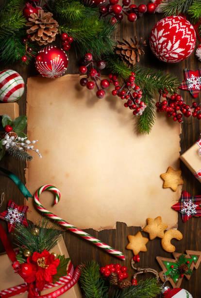 Rahmen mit Vintage-Papier, Tannenzweigen, Plätzchen und Weihnachtsdekorationen auf dunklem Holzhintergrund. – Foto