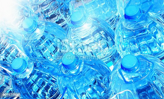 A background comprised of many blue plastic bottles of water, brightly lit.