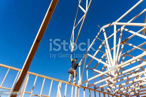 A Framer Standing On The Skelton Walls Of A New Home Construction Guiding The Crane Operator To Set Another Truss