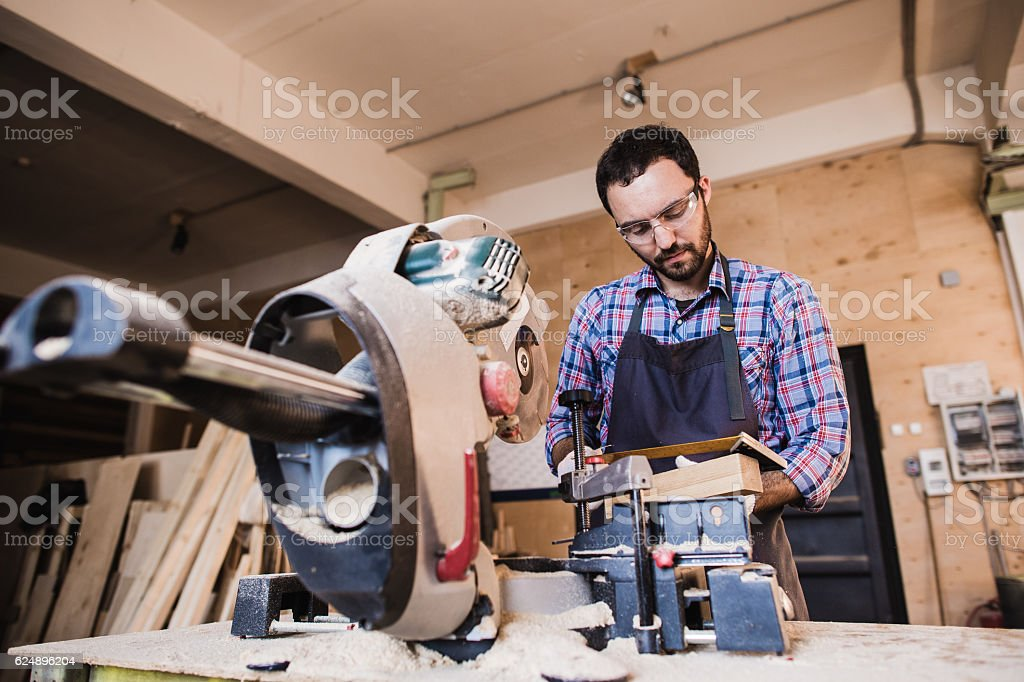 Framing contractor using a circular cut off saw to trim stock photo