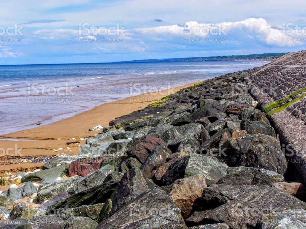 France, Calvados, Colleville sur Mer, Omaha Beach, Beach of the Landing rocks and ocean, blue sky and clouds stock photo