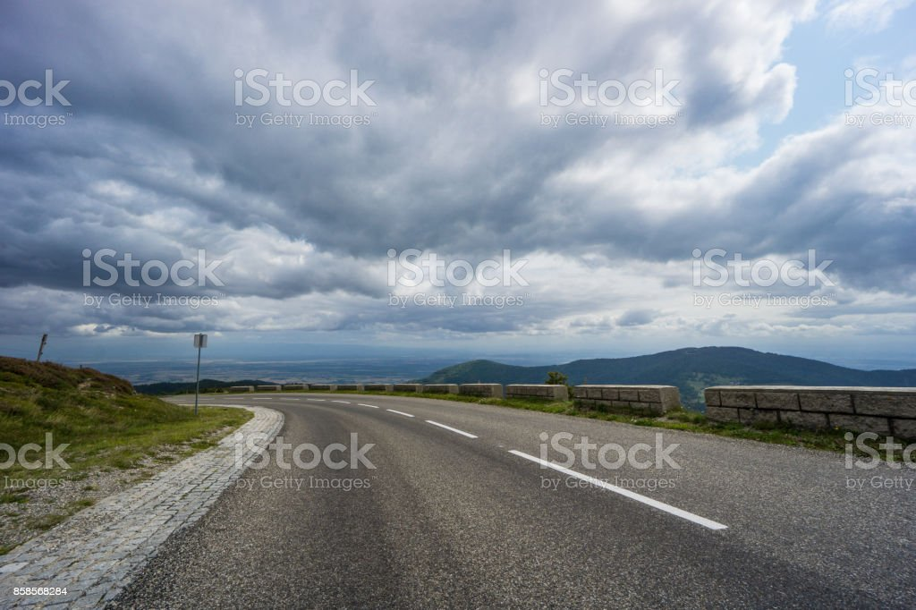 France - Left turn street of route de cretes with wide flat and mountain landscape behind stock photo
