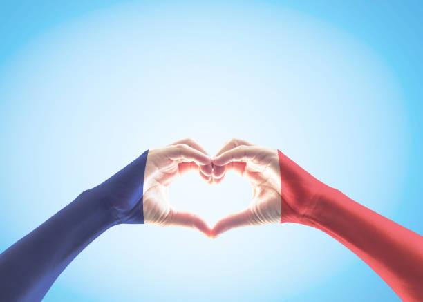 frankreich national flagge muster auf den händen der menschen in herzform auf blauen himmelshintergrund (isoliert mit clipping-pfad) - freistaat stock-fotos und bilder