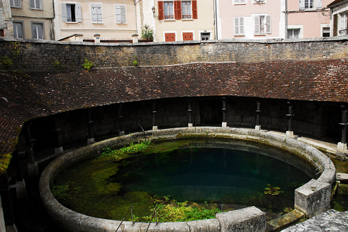 Panorama of the famous ancient historic karst spring of Fosse Dionne in the center of the village of Tonnerre in the Yonne region of France. Note the surrounding wash house structure and reflections.