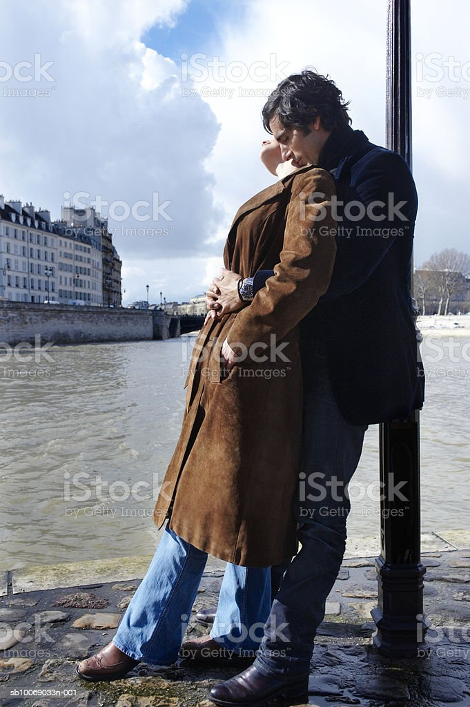 France, Paris, couple leaning against lamp post on riverbank, side view foto de stock libre de derechos
