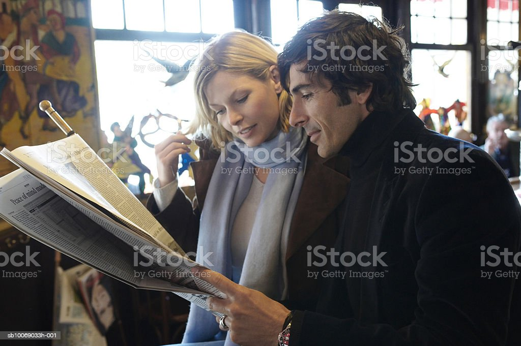 France, Paris, couple reading newspaper in cafe 免版稅 stock photo