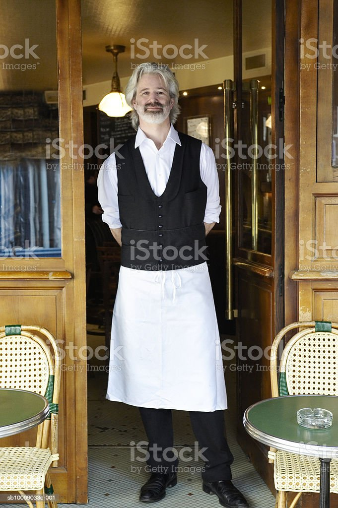 France, Paris, portrait of waiter standing in cafe door foto de stock libre de derechos