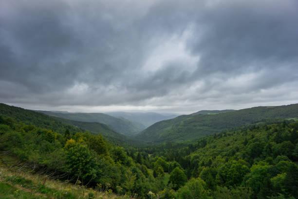 france - vallée entre les montagnes boisées des vosges français en alsace - orage en alsace photos et images de collection