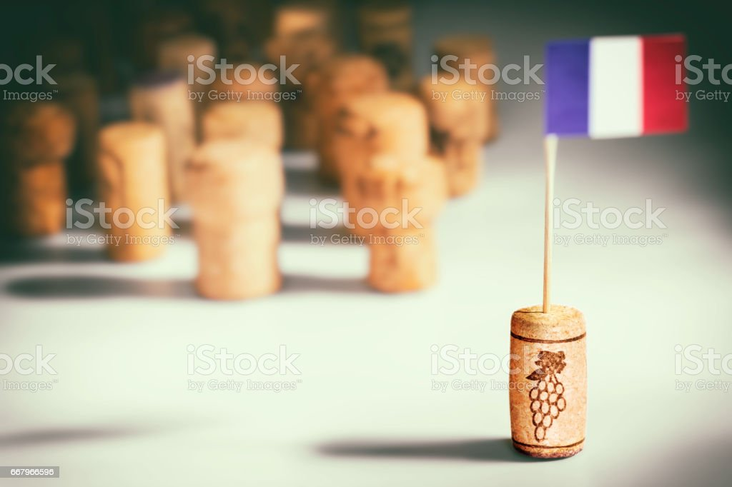 France wine industry with one wine cork bottle stopper with French flag planted in it and multiple corks in background - Photo