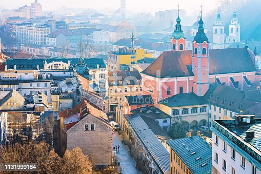 Franciscan Church and cityscape of Ljubljana old town streets, Slovenia in morning. Cathedral towers and beautiful Slovenian city view in winter. Skyline scenery and landmark. Urban green capital.