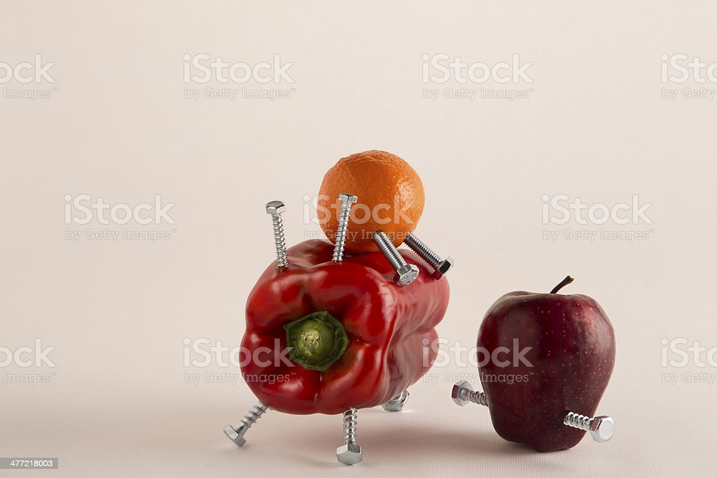GMO Frankenfood: pepper, mandarin, apple and bolts royalty-free stock photo