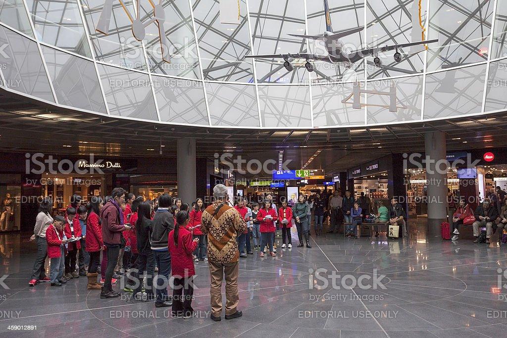 Frankfurt Airport. Choir with asian children entertaining. royalty-free stock photo