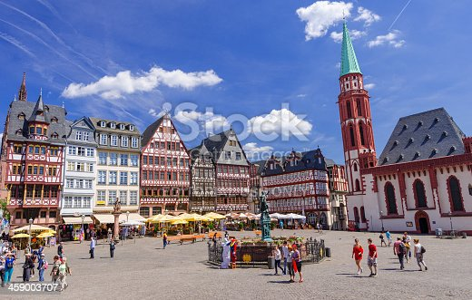Frankfurt, Germany - May 29, 2012: Scenery at the Römerberg on a beautiful summer day in Frankfurt, Germany. The Römerberg is the historical square in the old town of Frankfurt and the city´s major tourist attraction. The original half-timbered houses at the east row have been destroyed during the 2nd World War bombing in 1944 and were rebuilt in the 1980th. The east side of the square consist of the Cathedral (Kaiserdom Sankt Bartholomäus) on the left, the reconstructed half-timbered houses, the Fountain of Justice and the church of St. Nicolas on the right.