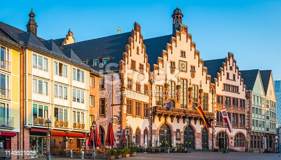 Warm light of daybreak illuminating the medieval facade of Romer City Hall overlooking the plaza of Romerberg in the historic Alstadt district of Frankfurt am Main, Germany.
