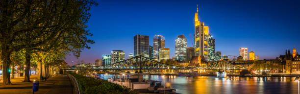 Frankfurter Wolkenkratzer glitzern bei Einbruch der Dunkelheit über den Main – Foto