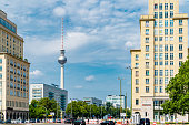 Cars passing Frankfurter Allee surrounded by Stalinist Empire style buildings. Fernsehturm (Berlin TV tower) on the background.
