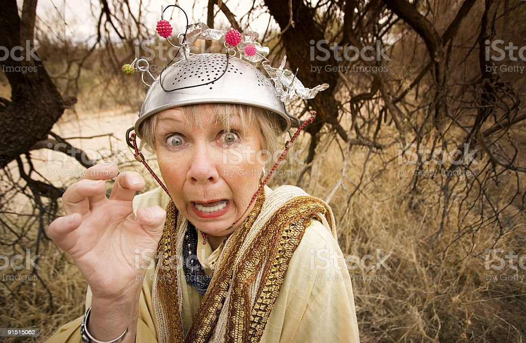 Frantic woman wearing a colander on her head stock photo