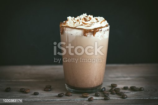 Cold Frappe Coffee (frappuccino) with whipped cream and caramel on dark background, copy space.