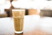 Close up shot of a coffee frappe. Coffee frappe is a cold variation of instant coffee drink with foam being whizzed out of coffee and milk added with lots of ice and water.