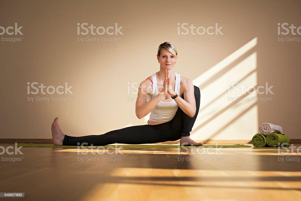 Frau die Yoga macht auf einer Yogamatte stock photo