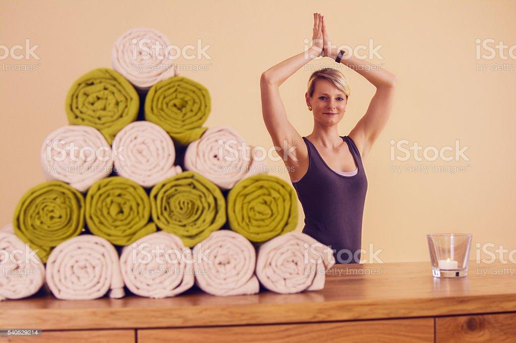Frau die Yoga macht mit Vordergrund kasten und handtücher stock photo