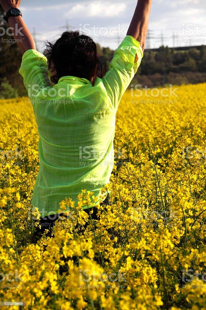 Frau läuft durch ein Rapsfeld stock photo