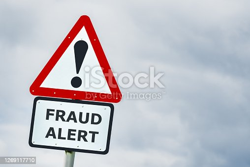 Conceptual triangular hazard road sign against a stormy sky saying fraud alert
