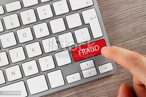 Index finger is pushing 'Fraud' button on computer keyboard