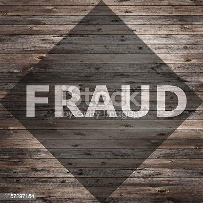 istock Fraud text on seasoned wood background. 1157297154