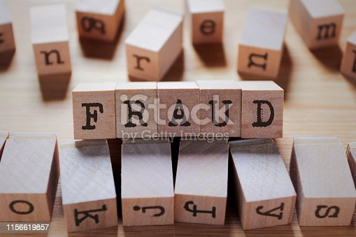 istock Fraud Word In Wooden Stamp Cube 1156619857