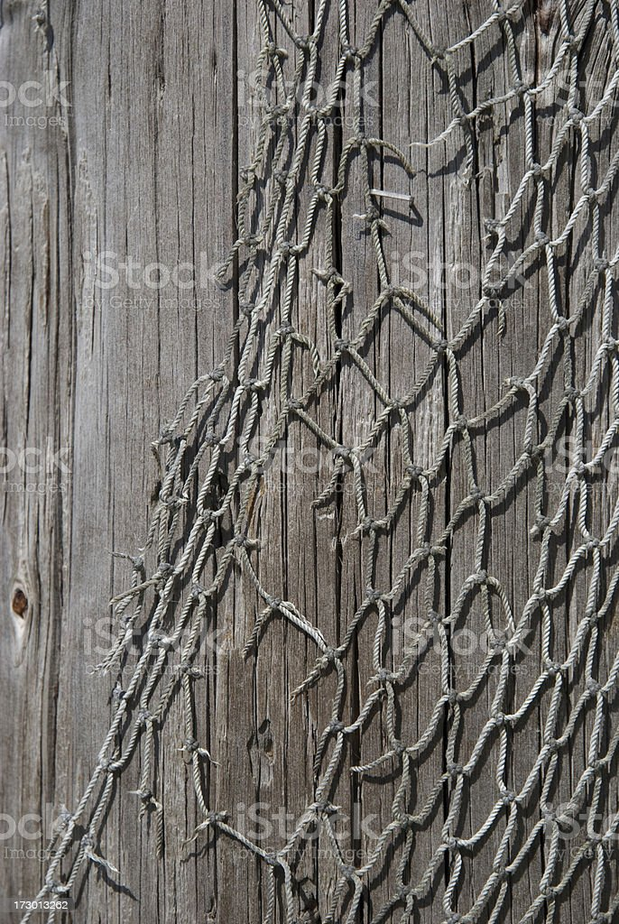 frayed and weathered old fishing net on a pier support stock photo