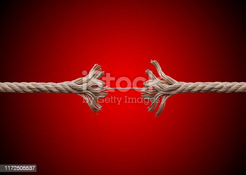 Frayed rope about to break on red background.