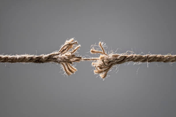 Frayed rope about to break Frayed rope about to break concept for stress, problem, fragility or precarious business situation fragility stock pictures, royalty-free photos & images