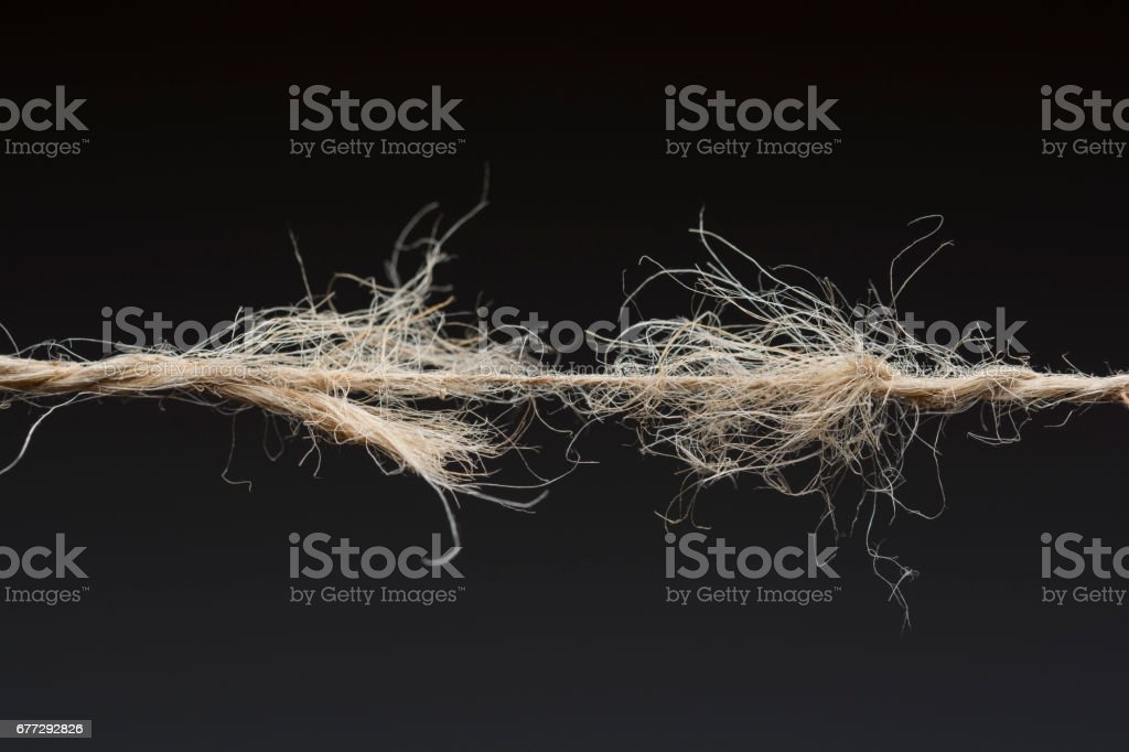 Frayed rope ready to break on dark background stock photo