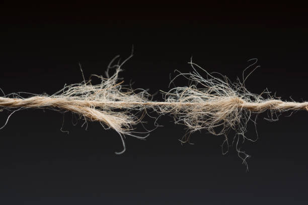 Frayed rope ready to break on dark background Frayed rope ready to break on dark background snapping stock pictures, royalty-free photos & images