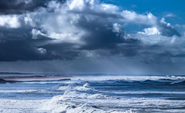 Freak waves breaking on rocky shore under dramatic sky stock photo