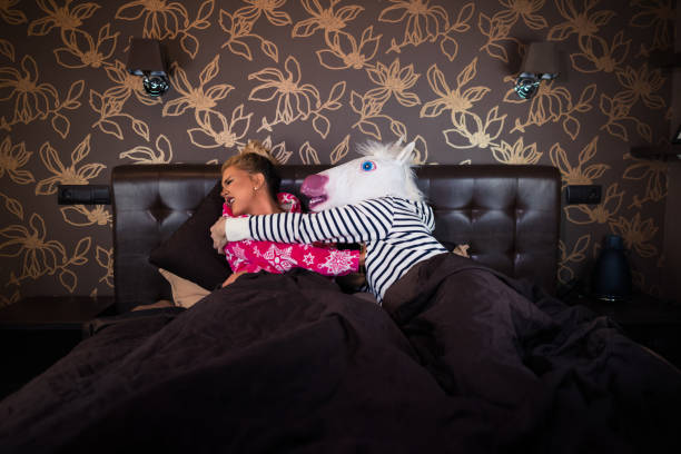 freaky man in unicorn mask molest to scared girlfriend in pajama in bed - unicorn bed imagens e fotografias de stock