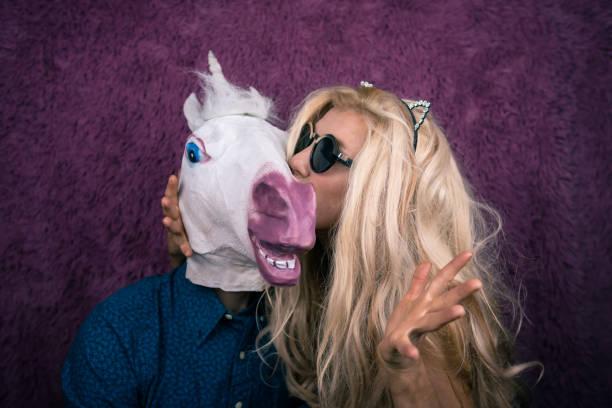 ausgeflippte junge frau mit sonnenbrille und kitty ohren küssen glücklich einhorn - freund kostüme stock-fotos und bilder