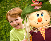Smiling redhead freckle face boy, laughing child with autumn scarecrow. (SEE LIGHTBOXES BELOW for many more photos of this model & sibling, Halloween holiday costumes & food photos...)