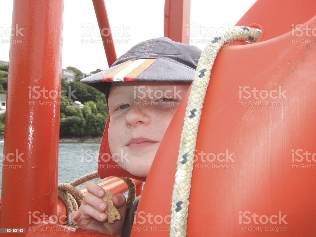Freckled boy looking through Lifering royalty-free stock photo