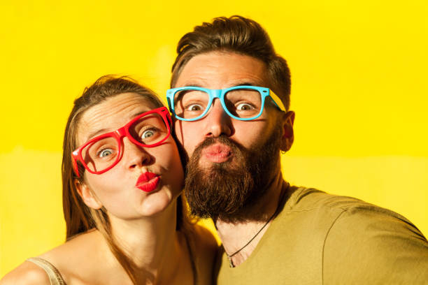 freckled woman, and bearded man send air kissing at camera - brunette woman eyeglasses kiss man foto e immagini stock