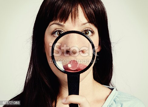A young brunette beauty looks shocked as she examines her nose through a magnifying glass, discovering freckles or - worse - blackheads!