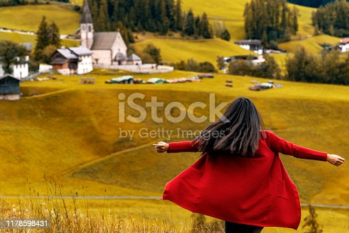 Young woman with open arms, standing while looking at Superb morning scene of Compaccio village, Seiser Alm or Alpe di Siusi location, Bolzano province, South Tyrol, Italy, Europe. Colorful summer sunrise of Dolomiti Alps.