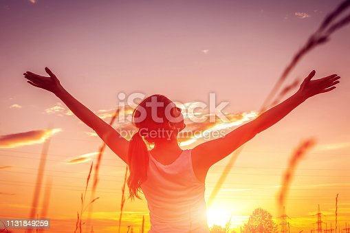 Free and happy woman raises arms against the sunset sky. Harmony and balance concept