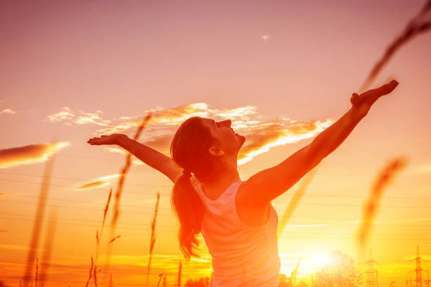 Free and happy woman raises arms against the sunset sky. Harmony and balance stock photo