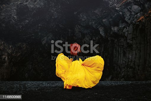 rear view of model running in the wilderness with yellow dress flying. location - basalt columns in Iceland.